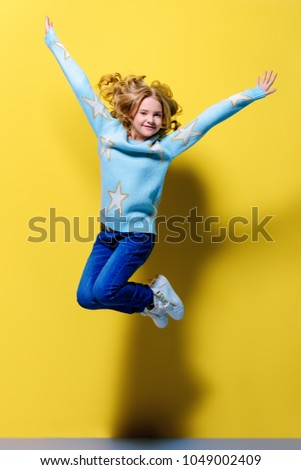 Joyful pre-teen girl jumping over yellow background. Full length studio shot. Happiness, activity and child concept. #1049002409