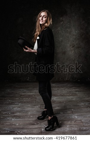 Joyful pretty girl wearing black classic hat smiling at camera #419677861
