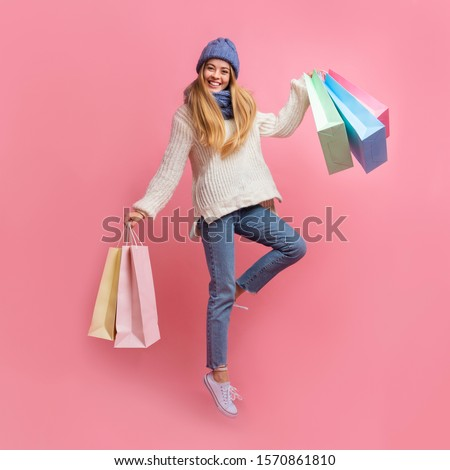 Joyful pretty winter girl carrying purchases and jumping up over pink background