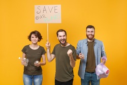 Joyful protesting people hold protest broadsheet placard bottles, trash bag doing winner gesture isolated on yellow background. Stop nature garbage ecology environment protection concept. Save planet