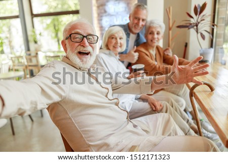 Joyful senior man spending time with friends stock photo