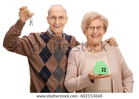 Joyful seniors with a pair of keys and a model house isolated on white background