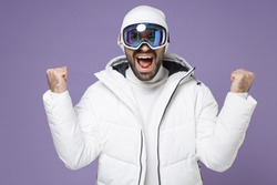 Joyful skier man in warm white windbreaker jacket ski goggles mask doing winner gesture spend extreme weekend winter season in mountains isolated on purple background. People lifestyle hobby concept