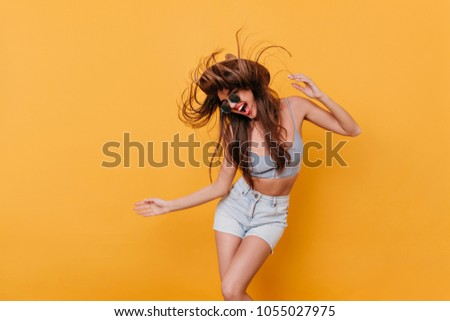 Joyful slim girl in blue shorts dancing with pleasure. Long-haired young woman in summer outfit having fun on yellow background.