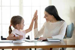 Joyful small daughter giving high five to satisfied with homework results mother. Happy young mom teacher babysitter praising little preschool child girl for making right tasks, sitting at home.