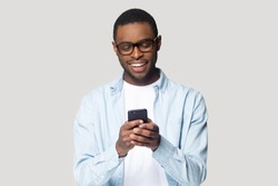 Joyful smiling african american young man in eyeglasses holding cellphone in hands, typing message, chatting with friends in social networks, playing online game, isolated on grey studio background.