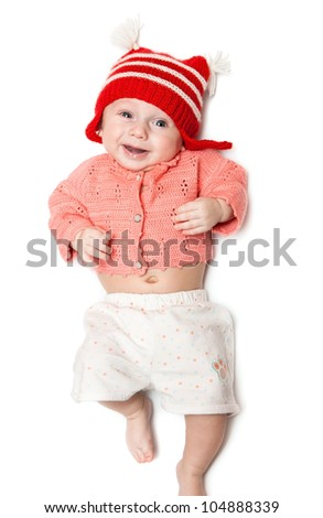 joyful smiling baby in red hat on white