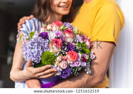 Joyful smiling girl holding different flowers and being embraced by her boyfriend wearing yellow t-shirt