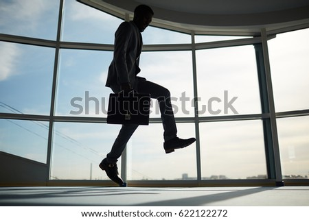 Joyful specialist with briefcase jumping in office #622122272