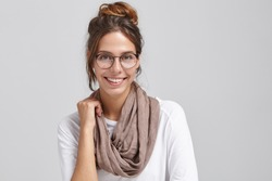 Joyful successful young European female artist or worker of creative profession wearing stylish round glasses and scarf around her neck, looking at camera and grinning broadly, showing white teeth