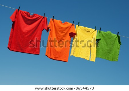 Joyful summer laundry. Colorful t-shirts on a laundry line and blue sky. #86344570