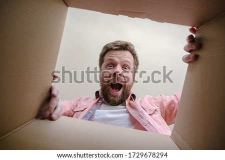 Joyful, surprised Caucasian man unpacks a delivered box with a parcel or a gift. Unboxing inside view.