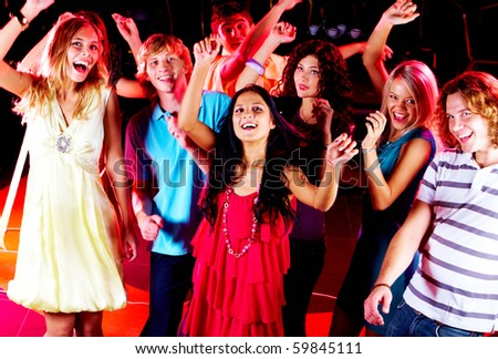 Joyful teens dancing in night club at party