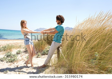 Joyful tourist couple enjoying a summer holiday together on beach with blue waters and grass sand dunes, holding hands being playful in a romantic summer honeymoon, outdoors nature. Travel lifestyle.
