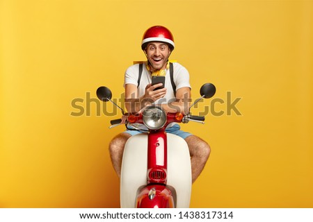 Joyful unshaven man sits on moped, wears red headgear, uses smartphone for communication on navigation, types message in motorbike service, happy to solve problem. Driving, technology concept