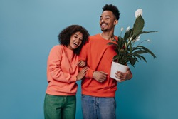 Joyful woman and man in orange sweatshirts smiling and posing with plant. Dark-skinned brunette girl in green jeans and guy in denim pants hold flower and hug