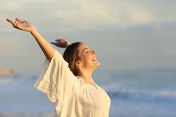 Joyful woman enjoying a day on the beach raising arms at sunset