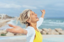 Joyful woman enjoying the freedom of the beach standing with open arms and a happy smile looking up towards the sky