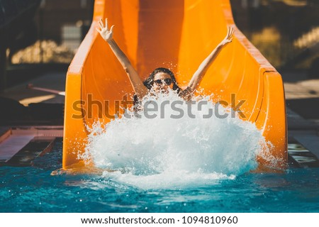 joyful woman going down on the rubber ring by the orange slide make the water splashing in the aqua park. Summer Vacation. Weekend on resort