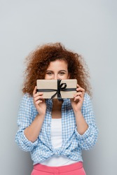 joyful woman obscuring face with gift box while looking at camera isolated on grey