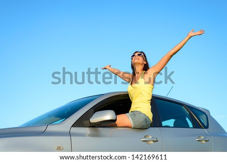 Joyful woman sitting on window new car raising arms up to the sky on summer trip. Blissful and fun happy girl on travel vacation. - stock photo