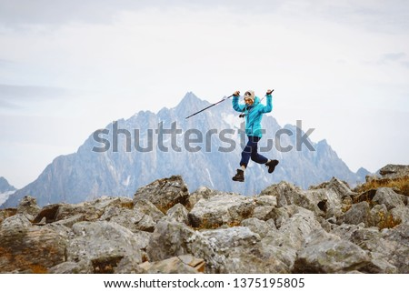 Joyful woman tourist jumping for joy in the mountains #1375195805