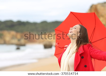 Joyful woman wearing red jacket breathing fresh air excited with an umbrella on the beach