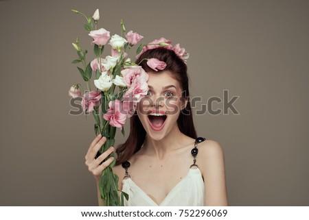 joyful woman with flowers on a light background                                #752296069