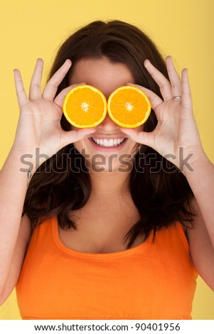 Joyful Woman With Orange Slices Over Eyes on orange studio background