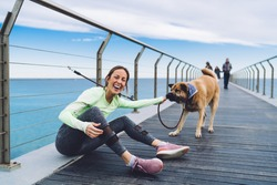 Joyful 40 years old female in sport clothes playing with leash and dog and laughing while looking at camera on pier