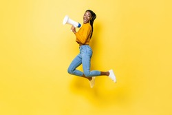 Joyful young African American woman holding megaphone jumping and making announcement in isolated studio yellow background