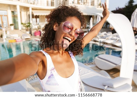 Joyful young african woman in swimsuit taking a selfie while spending good time a swimming pool resort