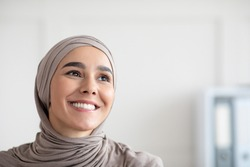 Joyful young arab woman in hijab smiling and looking at copy space, closeup portrait, panorama. Muslim lady posing in office. Gender equality, working opportunities for women in islam concept
