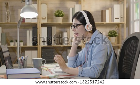 Joyful young asian woman wearing headset with microphone sitting at the desk at home opposite computer enjoy music and singing. Student studying online e-learning has a break sing songs with laptop. #1322517242