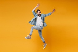 Joyful young bearded man in casual blue shirt posing isolated on yellow orange wall background studio portrait. People sincere emotions lifestyle concept. Mock up copy space. Jumping, rising hands up