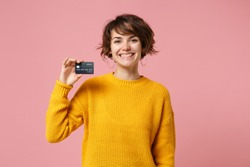 Joyful young brunette woman girl in yellow sweater posing isolated on pastel pink wall background studio portait. People sincere emotions lifestyle concept. Mock up copy space. Hold credit bank card