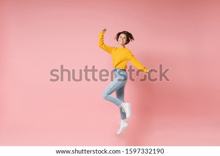 Joyful young brunette woman girl in yellow sweater posing isolated on pastel pink wall background. People lifestyle concept. Mock up copy space. Having fun fooling around jumping doing winner gesture