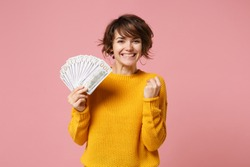 Joyful young brunette woman in yellow sweater posing isolated on pastel pink background. People lifestyle concept. Mock up copy space. Hold fan of cash money in dollar banknotes, doing winner gesture