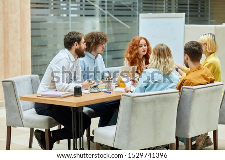 Joyful young colleagues, casually dressed, discuss new design project, sitting at wooden table in fashionable gray armchairs, busy at work, left side shot