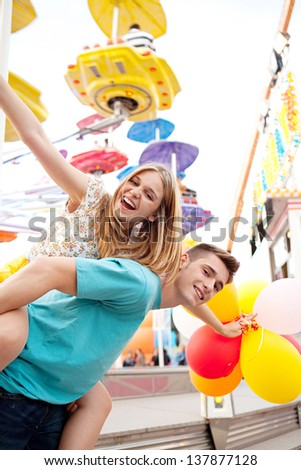 Joyful young couple being playful while visiting an attractions park arcade with rides, with young man giving girl a piggy bag and having fun.