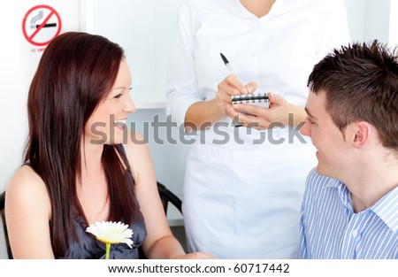 Joyful young couple dining at the restaurant with waiter taking order