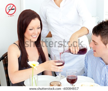 Joyful young couple having dinner at the restaurant with waiter serving them wine
