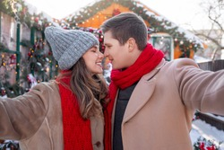 Joyful young couple in warm outfits bonding and taking selfie outdoors, enjoying sunny winter day together. Portrait of happy man and woman looking at each other and taking photo