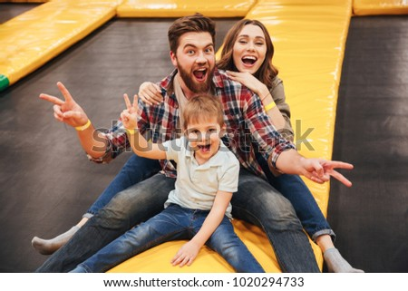 Joyful young family with their little son spending time on a trampoline together at the entertainment centre
