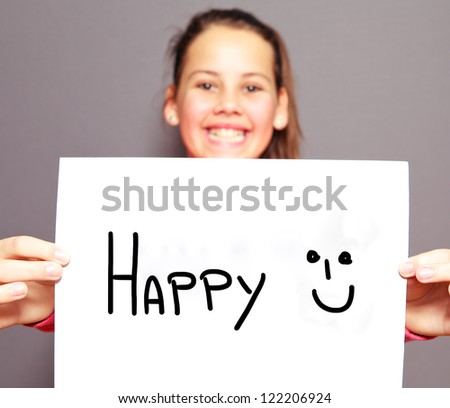 Joyful young girl with a HAPPY sign and smiley face handdrawn on a sheet of white paper with focus to the message