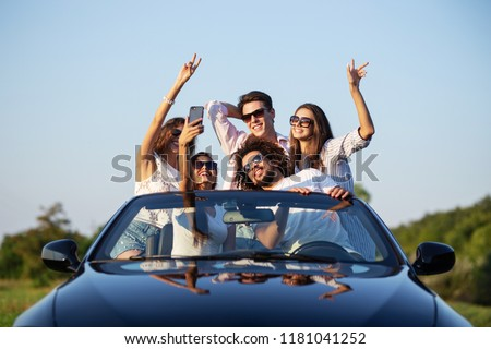 Joyful young girls and guys in sunglasses are sitting in a black cabriolet on the road holding their hands up and making selfie on a sunny day.