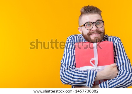 Joyful young hipster guy with a mustache in glasses hugs a red gift box on a yellow background with copy space. The concept of the joy of gifts.