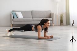 Joyful young lady in sportswear planking in living room, watching fitness video or having video conference with fitness trainer, sporty woman exercising and watching at smartphone screen, free space
