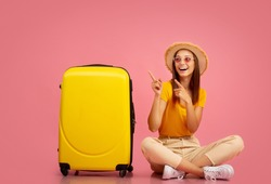 Joyful young lady in summer hat and sunglasses sitting on floor by luggage and pointing at copy space, pink studio background. Happy woman in summer clothes showing exciting travelling deals