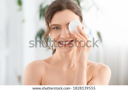Joyful young lady removing makeup from her eyes, covering one eye with cotton pad and smiling at camera. Closeup of cheerful woman with cotton pad, using micellar water for makeup removing